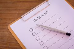 Checklist concept - checklist, paper and a pen with checklist word on wooden table.  royalty free stock image