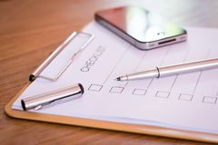 Checklist concept - checklist, paper and a pen with checklist word on wooden table.  royalty free stock photography