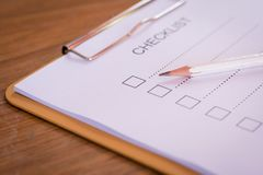Checklist concept - checklist, paper and a pen with checklist word on wooden table.  stock images