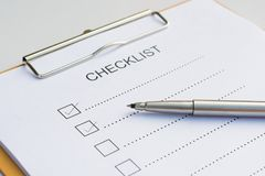 Checklist concept - checklist, paper and a pen with checklist word on wooden table royalty free stock photography