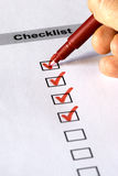 Checklist form. Close up of someone's hand writing in a checklist with red pen Royalty Free Stock Images