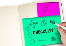 Checklist graphic on a post-it in a notebook. Hand with pen drawing it. Digital composite of Checklist graphic on a post-it in a notebook. Hand with pen drawing Stock Images