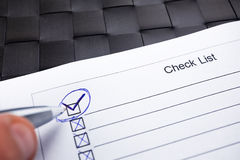 Checklist with hand doing tick mark with a pen. Stock Photos