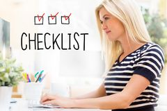 Checklist with happy young woman in front of the computer. Checklist with happy young woman sitting at her desk in front of the computer royalty free stock photography