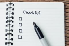 Checklist with marker pen and check box on small notepad on wood table, to do list, prioritize or reminder for project or plan.  stock images