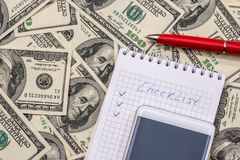 Checklist on a notepad with money and pen. Checklist on a notepad with money and pen royalty free stock photos