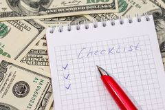 Checklist on a notepad with money and pen.  royalty free stock photography