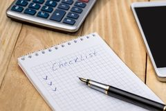 Checklist on a notepad with pen and calculator on desk.  stock photography