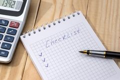 Checklist on a notepad with pen. And calculator on desk royalty free stock images