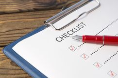 Checklist, pen fountain pen, sheet. Of paper on a wooden background. scroll royalty free stock photo