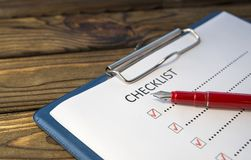 Checklist, pen fountain pen, sheet of paper. On a wooden background. scroll royalty free stock photography