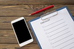 Checklist, pen fountain pen, sheet of paper on a wooden background. Smartphone with black screen for your text or design stock photos