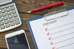 Checklist, pen with a fountain pen, a piece of paper on a wooden background. Calculator and smartphone with black screen for your text or design stock image