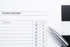 Checklist with a pen. Yes or no choice with elegantballpen on striped background royalty free stock images