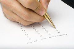 Checklist questionnaire quality of service. Businessman filling out a questionnaire quality of service Royalty Free Stock Photo