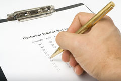 Checklist questionnaire quality of service. Businessman filling out a questionnaire quality of service Royalty Free Stock Image