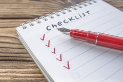 Checklist, red pen on the background. Of a wooden table. close-up royalty free stock images