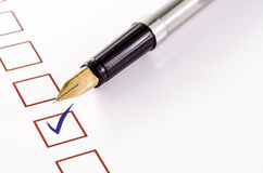 Checklist with a ticked box and a pen on white paper. Royalty Free Stock Photos