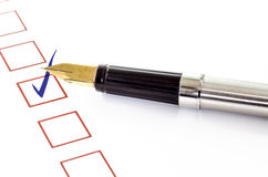 checklist with a ticked box and a pen on white paper. Royalty Free Stock Images