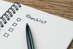 Checklist, to do list, prioritize or reminder for project plan, handwriting headline the word Checklist with black marker pen and. Check box on small notepad on stock photos