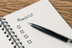 Checklist, to do list, prioritize or reminder for project plan, pen with handwriting headline the word Checklist and check box on. Small notepad on wood table stock photo