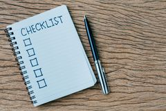 Checklist, to do list, prioritize or reminder for project plan, pen, notebook with handwriting headline the word Checklist and. Check box on wood table with stock photo