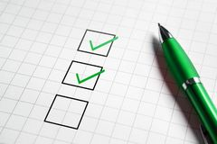 Checklist and to do list with v sign check marks in square box. Pen and paper. Project management, planning and keeping score of completed tasks concept stock images