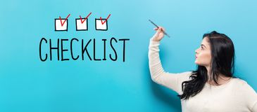 Checklist with young woman holding a pen. On a blue background stock image