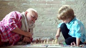 checkmate Милый мальчик играя шахматы o Концепция деда и внука Шахматная фигура Милый превращаться мальчика сток-видео