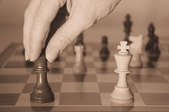 Checkmate. Woman's hand moving a chess piece into checkmate position. Sepia tone royalty free stock photos