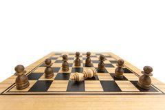Checkmate. Falling white king has threatened with capture by masses of pawns on wooden chess board, checkmate concept in chess game stock photography