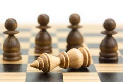 Checkmate. Falling white king has threatened with capture by masses of pawns on wooden chess board, checkmate concept in chess game royalty free stock image