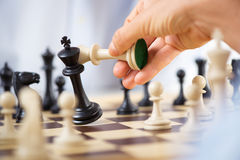 Checkmate. Man hand holding queen and king in checkmate position stock photos