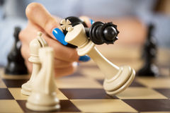 Checkmate. Woman hand holding queen and king in checkmate position stock photography