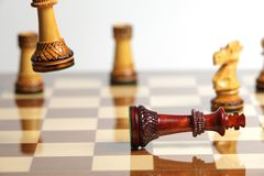Checkmate with wooden chess. Pieces on a reflective chessboard Royalty Free Stock Photography