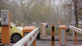 Checkpoint three posts. Automatic road barrier gate lifting gate opens and passes car.  stock footage