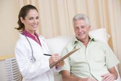 checkup clipboard doctor giving man to writing Στοκ εικόνα με δικαίωμα ελεύθερης χρήσης