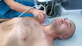 Man patient on preventive survey of thyroid gland using ultrasound scanner.