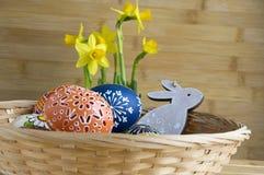 Checo feito a mão caseiro pintou os ovos e o coelho de madeira, pseudonarcissus amarelo do narciso na flor Imagem de Stock Royalty Free
