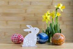 Checo feito a mão caseiro pintou os ovos e o coelho de madeira, pseudonarcissus amarelo do narciso na flor Imagens de Stock