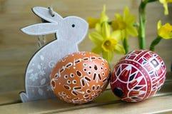 Checo feito a mão caseiro pintou os ovos e o coelho de madeira, pseudonarcissus amarelo do narciso na flor Fotografia de Stock