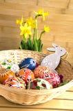 Checo feito a mão caseiro pintou os ovos e o coelho de madeira, pseudonarcissus amarelo do narciso na flor Imagens de Stock Royalty Free