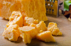 Cheddar Cheese. Chunks of cheddar cheese with grater on plain background Royalty Free Stock Photo