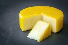 Cheddar Cheese on Black Slate. Aged cheddar cheese wheel on black slate Stock Photo