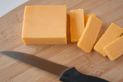 Cheddar Cheese Block and Slices. Cheddar cheese on a bamboo cutting board Stock Images