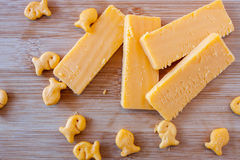 Cheddar Cheese Block and Slices. Cheddar cheese and fish crackers on a bamboo cutting board Stock Images