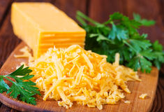 Cheddar cheese. On board and on a table royalty free stock photo