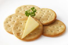 Cheddar Cheese and Crackers. Classic snack, cheddar cheese and crisp crackers on a white plate garnished with parsley. Clipping path included Stock Images