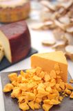 Cheddar Cheese Cubed. Aged orange cheddar cheese on a cheese table Royalty Free Stock Images