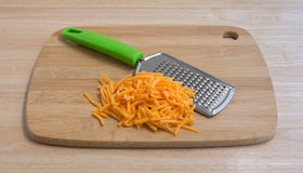 Cheddar cheese with grater on wood cutting board Stock Photos
